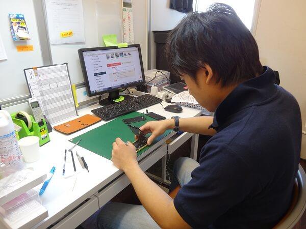 iPhoneを修理するスタッフ