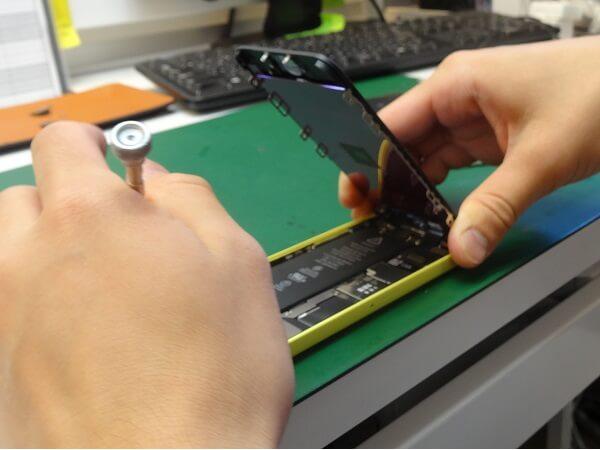修理中のために中を開くiPhone